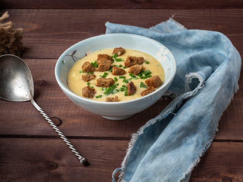 Ostsoppa mosade med smällare av mörkt bröd i en djupblå platta, en sked med ett vridet handtag och ett huvud av ung vitlök och royaltyfri fotografi