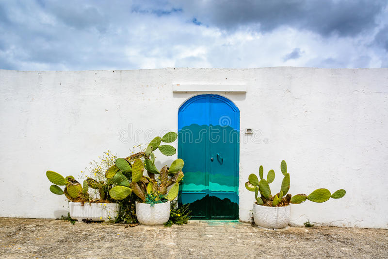 Ostuni, Puglia, Italy. Blue door and cactus on white wall in Ostuni, Puglia, Italy stock photo