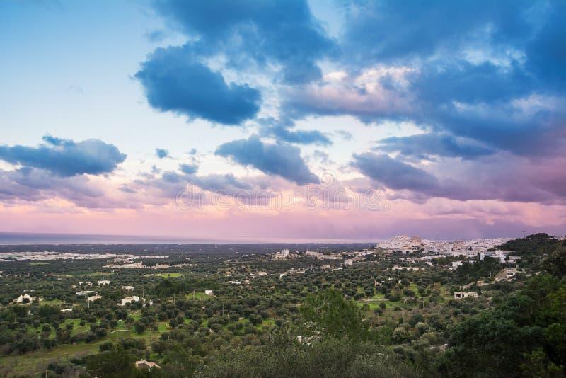 Ostuni y plantaciones de olivos en Puglia en la puesta del sol Italia imagen de archivo libre de regalías
