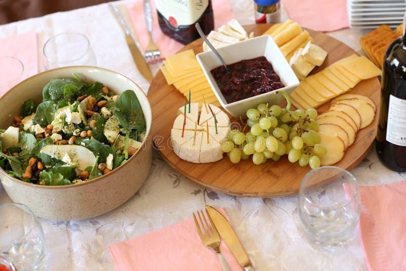ostuppläggningsfat med körsbärsröda sylter, druvor och olika ostar arkivfoton