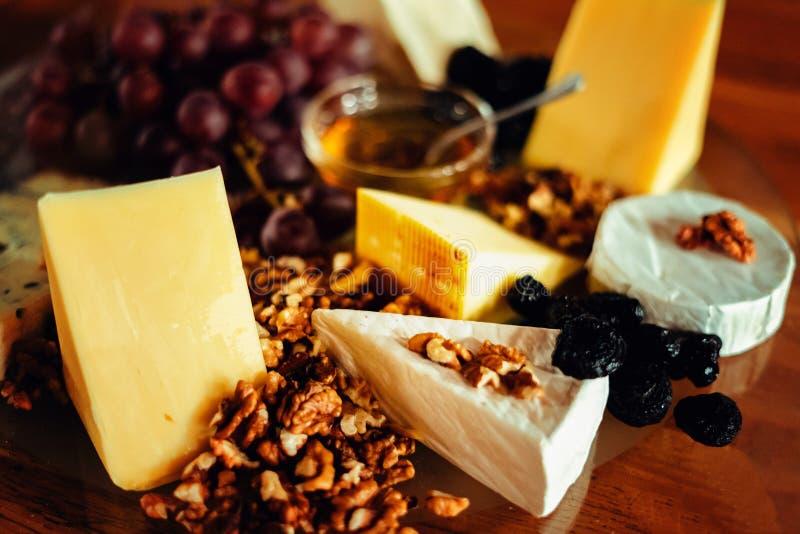 Ostuppläggningsfat med olika ostar, druvor, muttrar, honung, brea arkivfoto