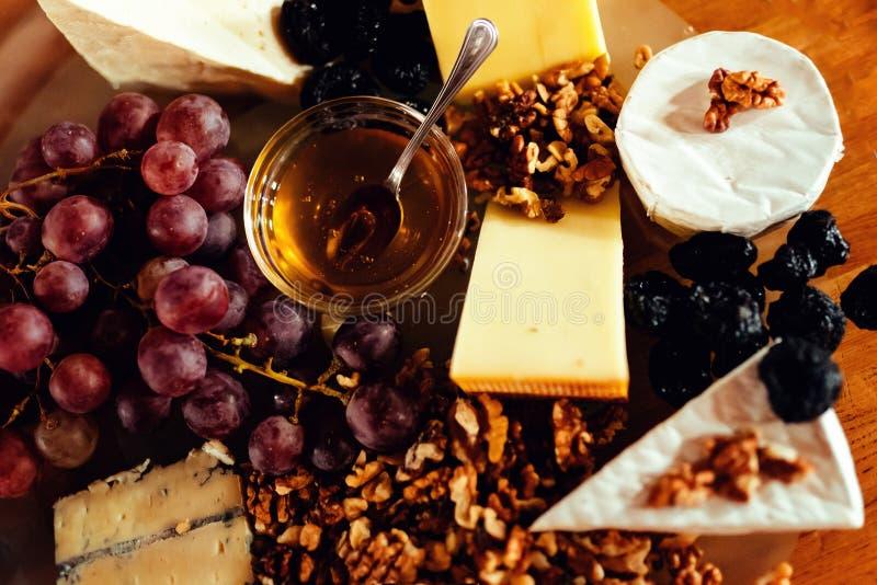 Ostuppläggningsfat med olika ostar, druvor, muttrar, honung, brea royaltyfri foto