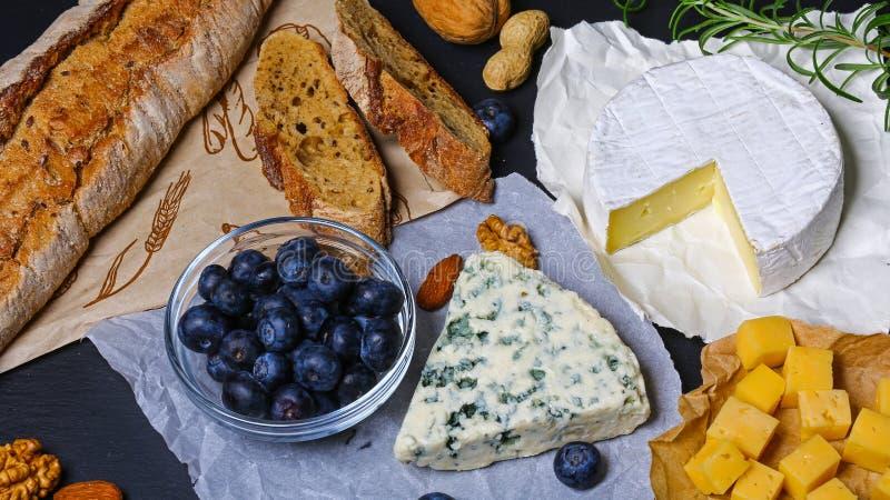 Ostuppläggningsfat på att smaka plattan med olika ostar - camembert, Dorblu, Brie Ost på en platta med örter, frukter och muttrar fotografering för bildbyråer