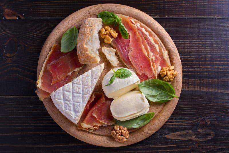 Ostval på trälantlig bakgrund Ostuppläggningsfat med den olika ostar, jamon eller prosciuttoen arkivfoton