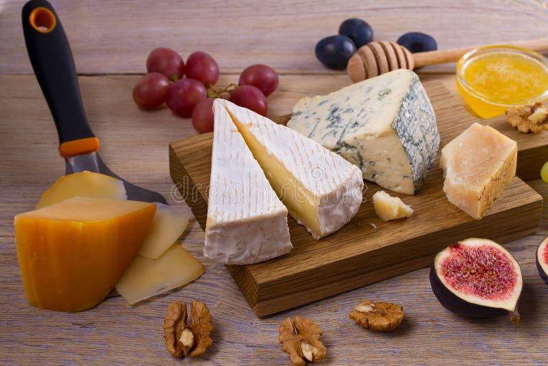 Ostval på trälantlig bakgrund Ostuppläggningsfat med olika ostar som tjänas som med druvor, fikonträd, muttrar och honung royaltyfri bild