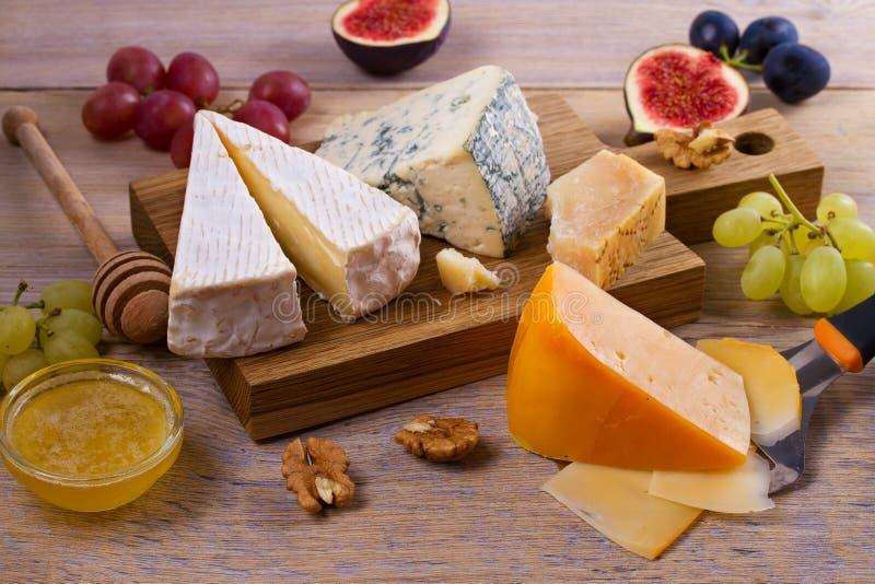 Ostval på trälantlig bakgrund Ostuppläggningsfat med olika ostar som tjänas som med druvor, fikonträd, muttrar och honung arkivfoto