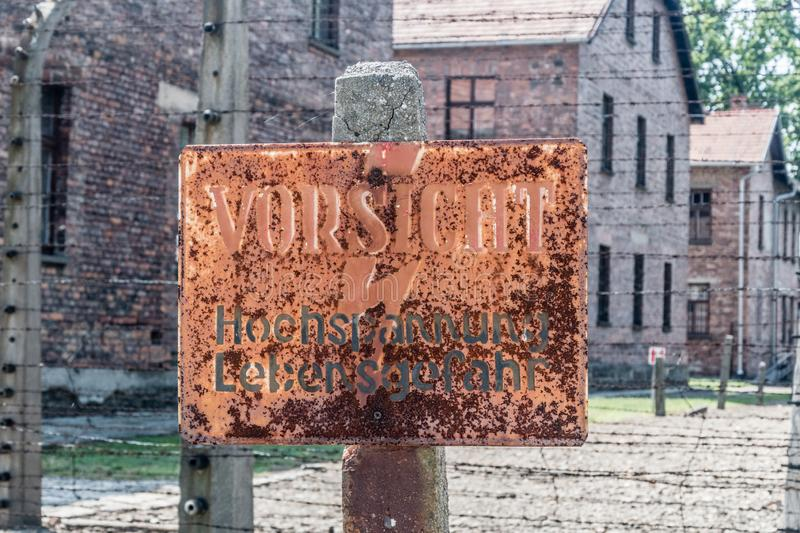 Electrified fence warning sign at Auschwitz I, Former German Nazi Concentration and Extermination Camp stock photo