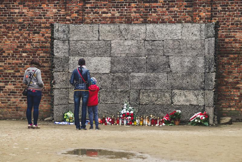 Visitors in front of death wall at concentration camp in Auschwitz I, Poland. OSWIECIM, POLAND - MAY 6: Visitors in front of death wall at concentration camp in stock images