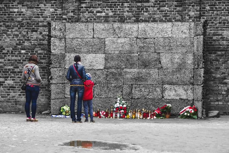 Visitors in front of death wall at concentration camp in Auschwitz I, Poland. OSWIECIM, POLAND - MAY 6: Visitors in front of death wall at concentration camp in royalty free stock images