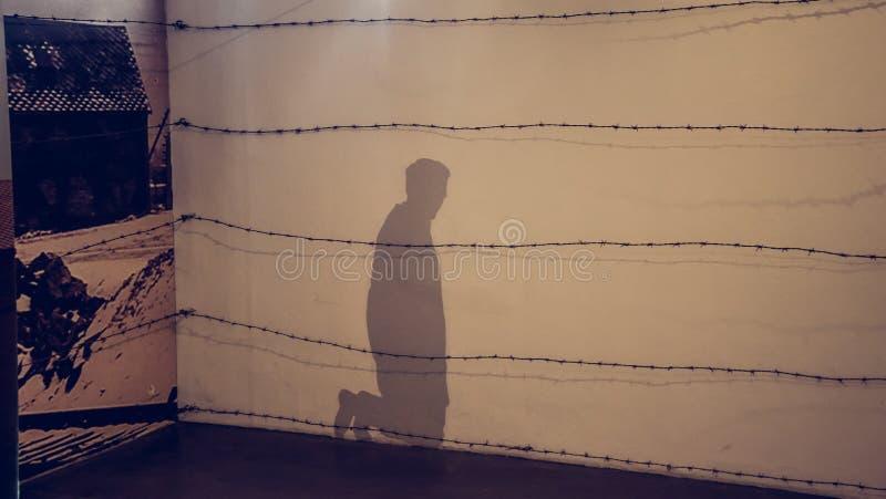 Oswiecim/Polonia - 02 15 2018: Sombra en la pared de un hombre de arrodillamiento fotos de archivo