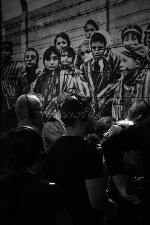Oswiencim, Polen - September 21, 2019: De toeristen nemen aan een rondleiding binnen de Auschwitz-gebouwen deel De Muren stock afbeelding