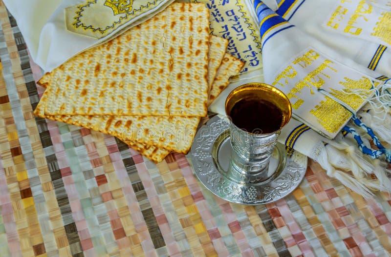 Osyrat bröd för judisk traditionell påskhögtid och en vinkopp med texten av den traditionella vinvälsignelsen royaltyfri fotografi