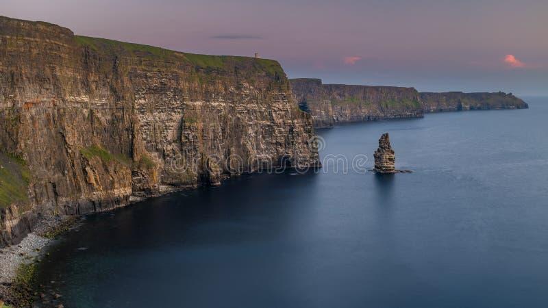 Oszałamiająco i majestatyczne falezy Moher w okręgu administracyjnym Clare, Irlandia przy zmierzchem, piękny różowy niebo obraz royalty free