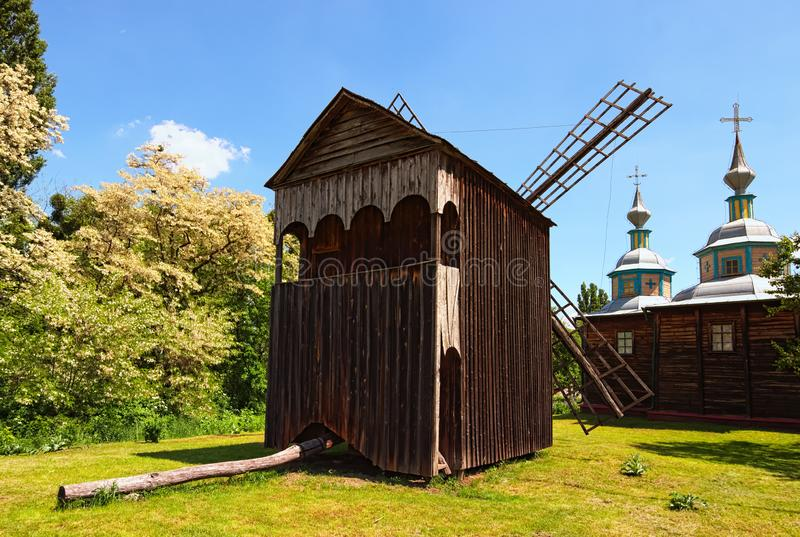 Oszałamiająco krajobrazowy widok drewniany antyczny wiatraczek i typowy drewniany kościół Pereyaslav-Khmelnitsky muzeum Ludowa ar zdjęcie stock