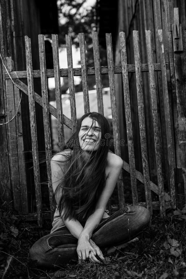 Oszałamiająco młoda szczęśliwa kobieta siedzi outdoors w wsi obrazy royalty free