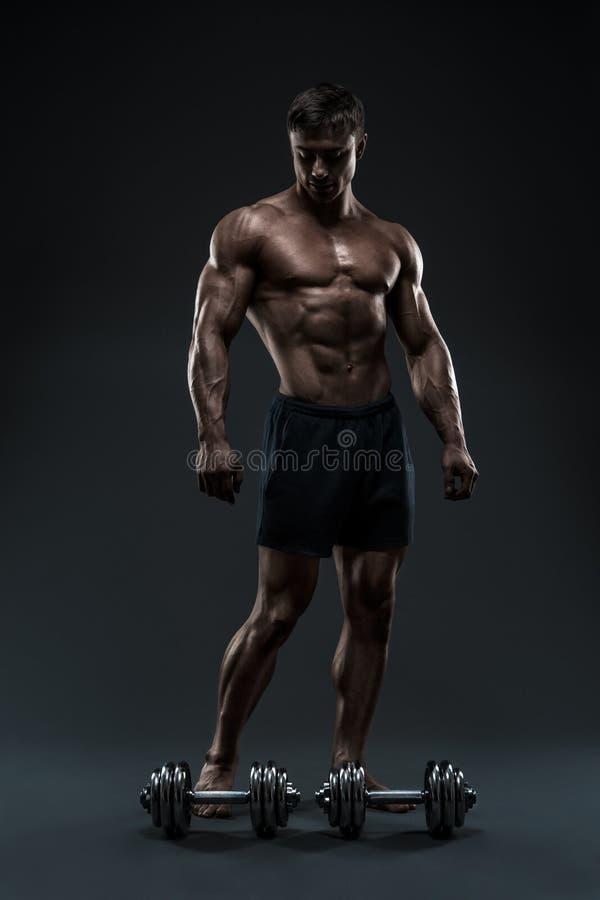 Oszałamiająco mięśniowy bodybuilder pozuje nad czarnym tłem zdjęcie royalty free