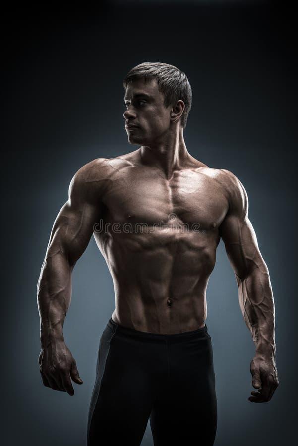 Oszałamiająco mięśniowy młodego człowieka bodybuilder patrzeje behind zdjęcia stock