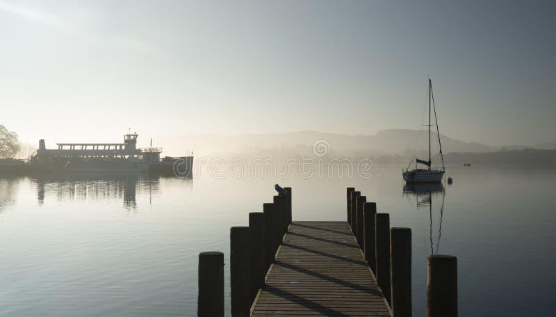 Oszałamiająco niezatamowany sztuka piękna krajobrazu wizerunek siedzi wciąż w spokojnej jezioro wodzie w Jeziornym okręgu podczas zdjęcia royalty free