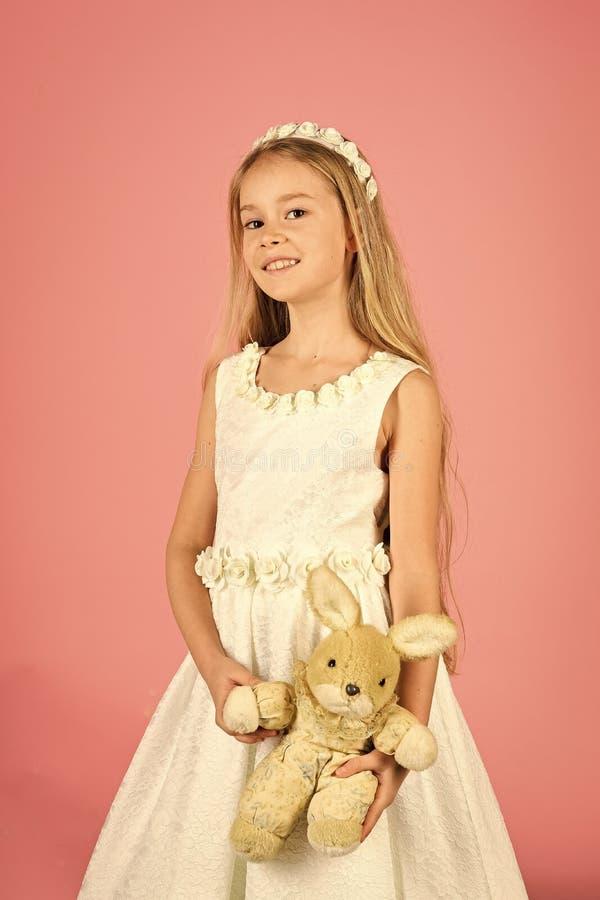 Oszałamiająco piękno młodej dziewczyny model w białych communion sukni stojakach w studiu z królik zabawką fotografia royalty free