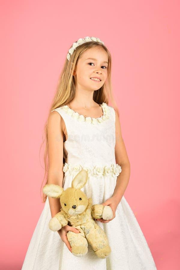 Oszałamiająco piękno młodej dziewczyny model w białych communion sukni stojakach w studiu z królik zabawką zdjęcia royalty free