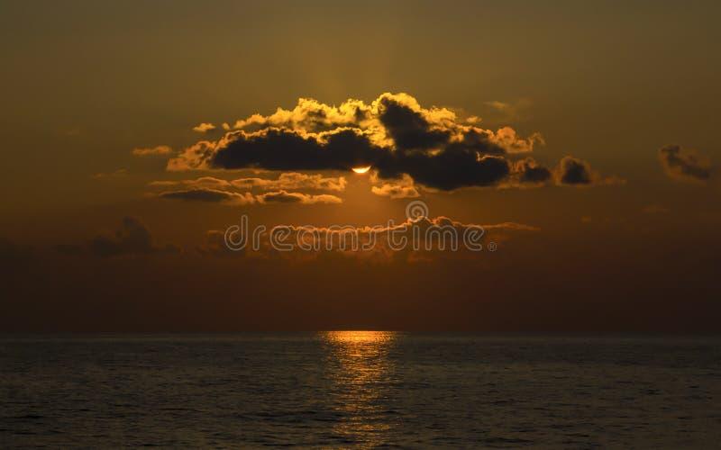 Oszałamiająco pomarańczowy zmierzch przy dennym jaskrawym słońcem tworzy słoneczną ścieżkę na spokojnej powierzchni zdjęcie stock