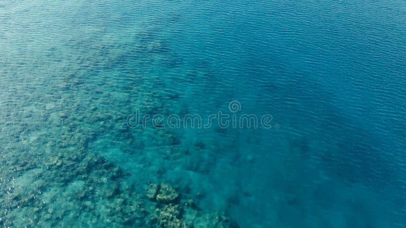 Oszałamiająco powietrzny trutnia wizerunek mały łodzi rybackiej wchodzić do obok rafy koralowej w kanale denny oceanu zakotwienie zdjęcia royalty free