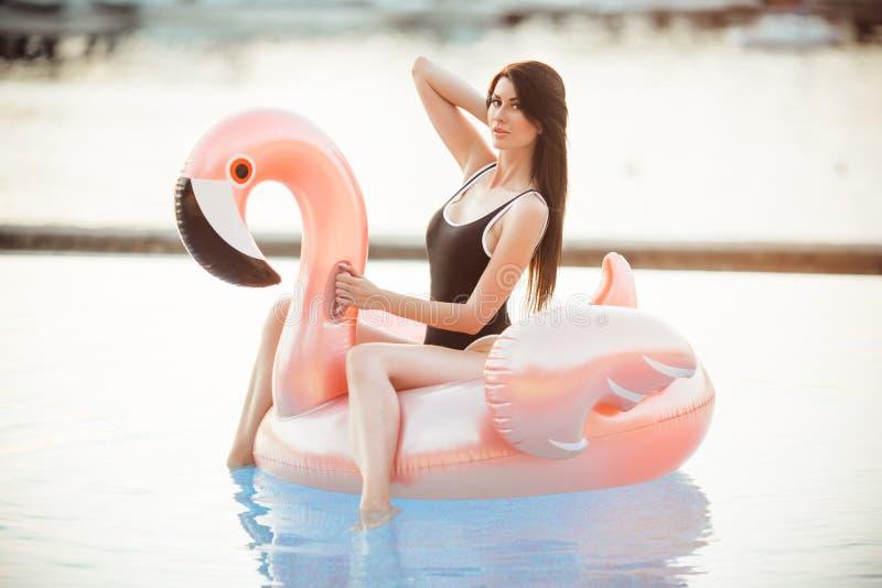 Oszałamiająco seksowna kobieta jest ubranym czarnego bikini obsiadanie w pływackim basenie z błękitne wody na różowej flaming mat zdjęcie royalty free
