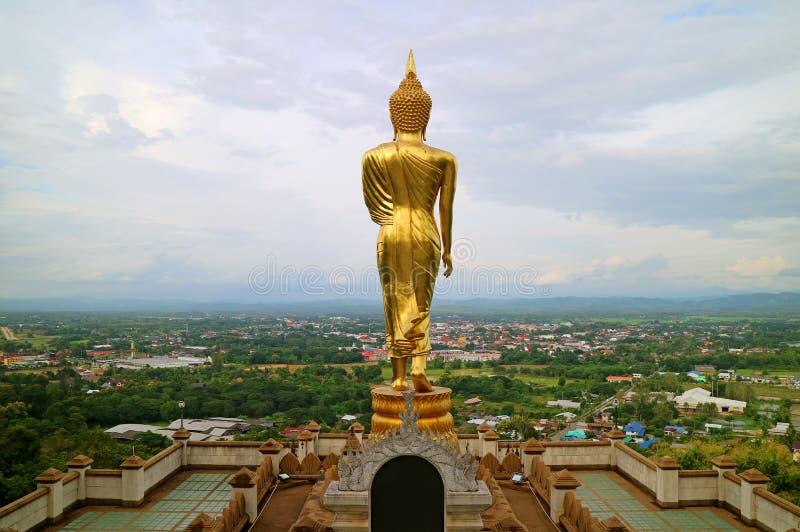 Oszałamiająco złoto barwił Buddha wizerunek w odprowadzenie posturze stawia czoło miasteczko Nan, Wat Phra Który Khao Noi świątyn zdjęcie stock