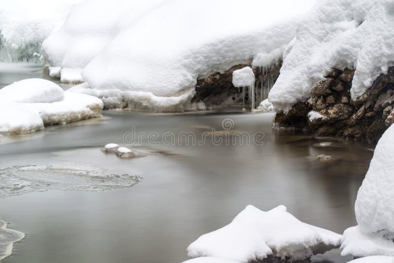 Oszałamiająco zima krajobraz, kamienie na mroźnej rzece zakrywał śnieg zdjęcie royalty free