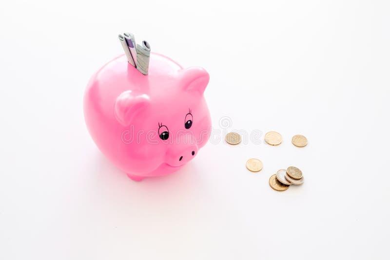 oszczędzania Moneybox w kształcie świnia z banknotami spada w je pobliskie monety na białej tło kopii przestrzeni obrazy royalty free