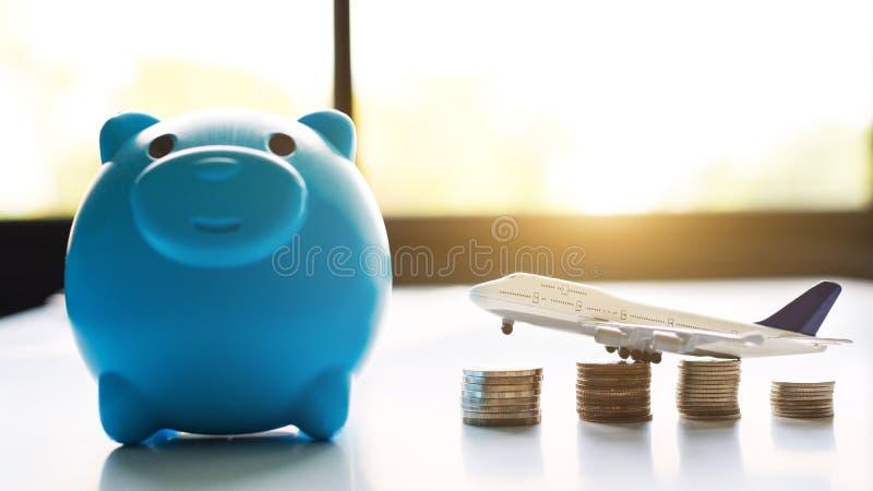 Oszczędzanie pieniądze dla podróży pojęcia Błękitny Peggy bank z samolotem i monetami zdjęcia royalty free