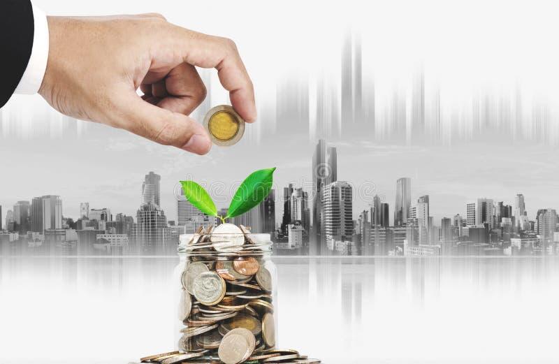 Oszczędzanie pieniądze i inwestyci pojęcie Ręki kładzenia moneta w szklanym słoju z rośliny dorośnięciem, miasta tło zdjęcie stock