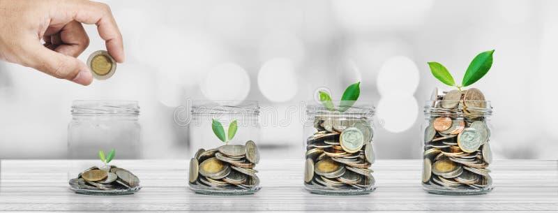 Oszczędzanie pieniądze i inwestycj pojęcia, ręki kładzenia moneta w szklanych butelkach z rośliien jarzyć się zdjęcia royalty free