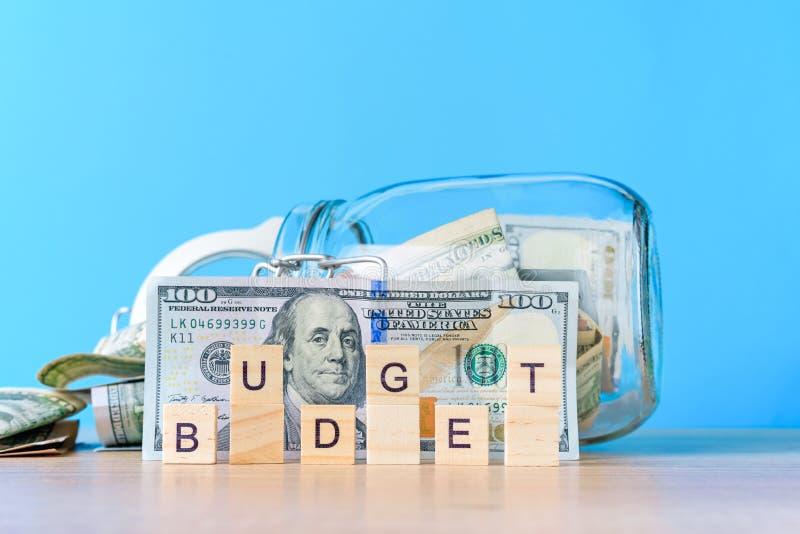Oszczędzanie pieniądze i planowanie budżeta pojęcie Dolarowi rachunki w szklanym oszczędzanie banku, słowie i budżetują na różowy obrazy stock