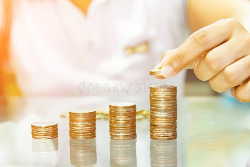 Oszczędzanie pieniądze, kobiety sztaplowania monety w wzrastające kolumny zdjęcie stock