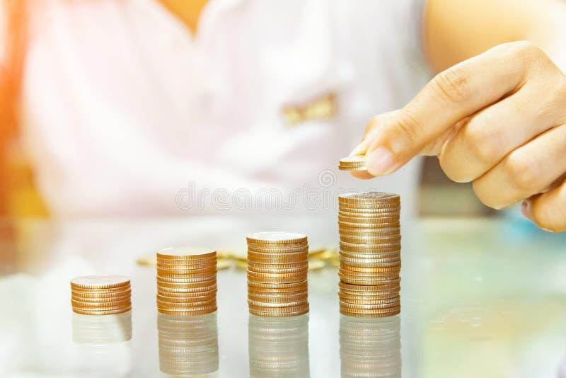 Oszczędzanie pieniądze, kobiety sztaplowania monety w wzrastające kolumny fotografia stock