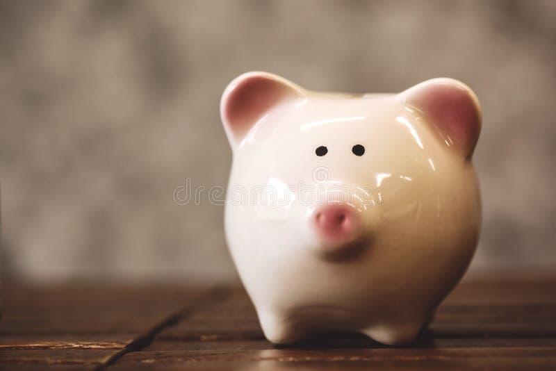 Oszczędzanie pieniądze pojęcie, monety w prosiątko banku obrazy royalty free