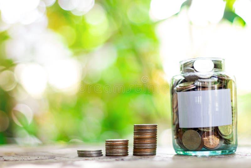 Oszczędzanie pieniądze w szklanej butelce Tło jest zielonym drzewa bokeh obrazy royalty free