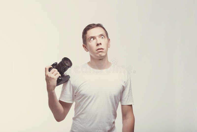 Oszołomiony Emocjonalny mężczyzna z kamerą odizolowywającą na lekkim tle Młodego człowieka mienia kamera z strabismus Styl życia, obrazy stock