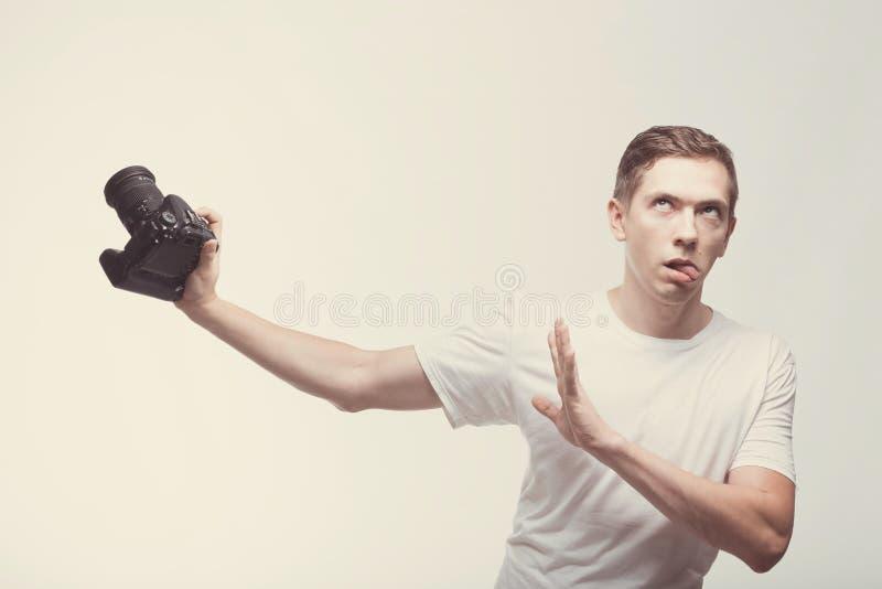 Oszołomiony Emocjonalny mężczyzna z kamerą odizolowywającą na lekkim tle Młodego człowieka mienia kamera z strabismus Styl życia, zdjęcia royalty free