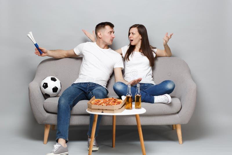 Oszołamiający pary kobiety mężczyzny fan piłki nożnej rozweselają w górę poparcie faworyta drużyny z drymbą, patrzeje each innego obrazy stock