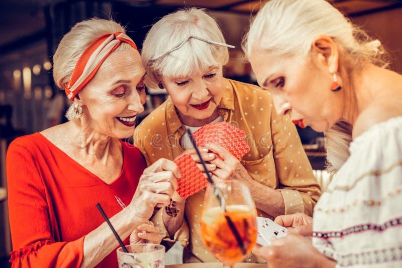 Oszukiwający uśmiechniętej starszej kobiety skrycie pokazuje ona karty zdjęcia stock