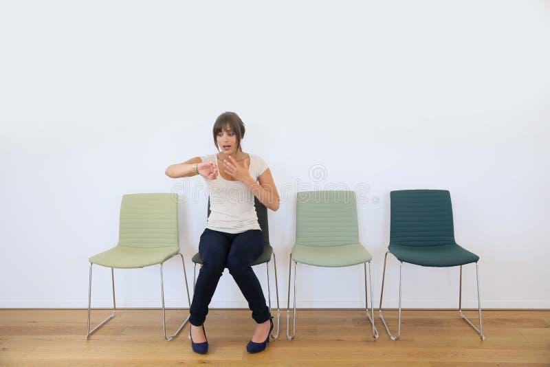 Otålig kvinna i väntande rum royaltyfri foto