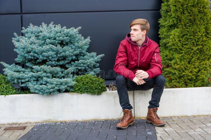 Otåligt sitta för tonåringpojke som är utomhus- parkerar in, borrad känsla arkivbild