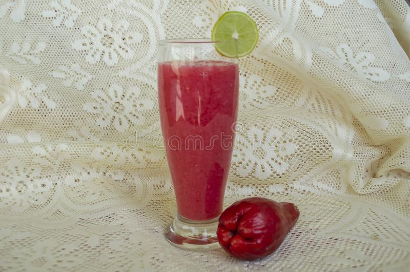 Otaheite Apple Smoothie. Sitting on a white lacey tablecloth are drinking glass filled with Otaheite apple smoothie garnished with a slice of ripe key lime, and stock photos