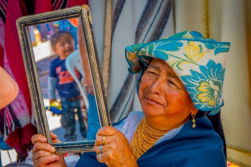OTAVALO, ECUADOR, IL 6 NOVEMBRE 2018: Chiuda su della donna indigena ispanica che tiene uno specchio per i clienti per provare il immagine stock libera da diritti