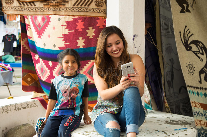 OTAVALO, ECUADOR - MAY 17, 2017: Beautiful young woman watching her cellphone next to an unidentified little indigenous royalty free stock image