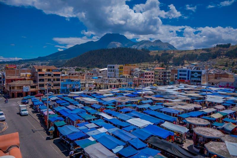 OTAVALO, ECUADOR, 06 NOVEMBER, 2018: Boven openluchtmening van vele die hutten in de straatmarkt worden gevestigd in Otavalo met  stock afbeelding