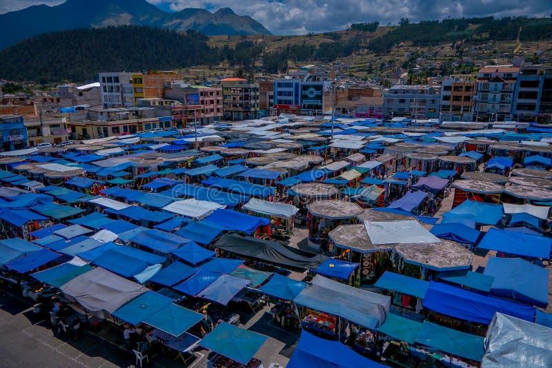 OTAVALO, ECUADOR, 06 NOVEMBER, 2018: Boven openluchtmening van vele die hutten in de straatmarkt worden gevestigd in Otavalo met  stock fotografie