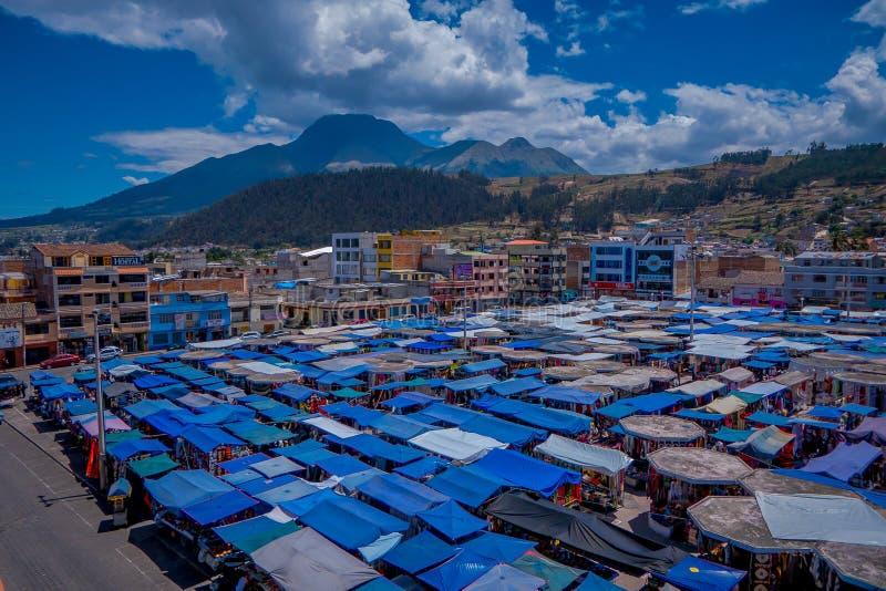 OTAVALO, ECUADOR, 06 NOVEMBER, 2018: Boven openluchtmening van vele die hutten in de straatmarkt worden gevestigd in Otavalo met  stock foto